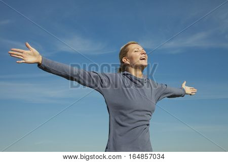 Side View Of A Young Woman Stretching Her  Against The Sky Bg