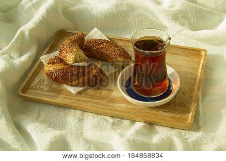 Morning tea Bagel and cup of turkish tea on the wood tray with Istanbul picture on the bedcover