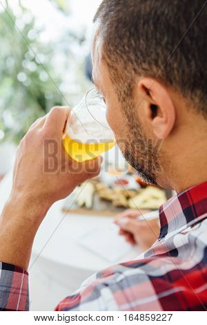 Bearded man drinking light craft beer.Overshoulder view.