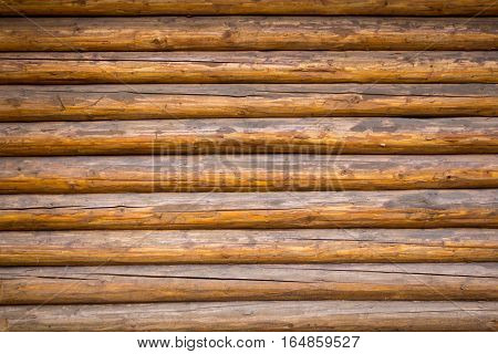 Wall from a large number of old brown logs