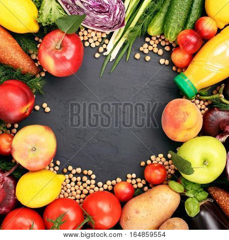 Frame of colorful variety foodstuffs on a dark background top view