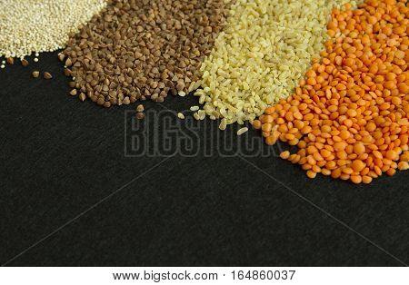 Four different groats: buckwheat lentil quinoa bulgur on black background