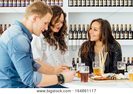 Smiling adult people estimating qualities of beer while sitting at table with beer and snacks
