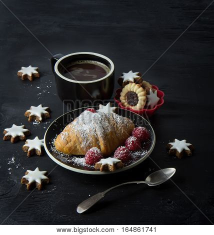 Still life with croissant cup of coffee and Christmas cookies on black background