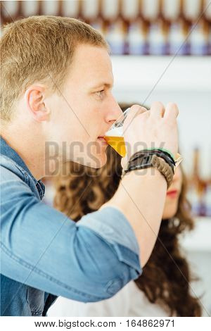Side view of handsome blond man drinking light craft beer