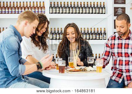 Smiling people estimating qualities of beer on a beer tasting