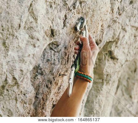 Female climber inserts a quickdraw in anchor on rock wall outdoor poster