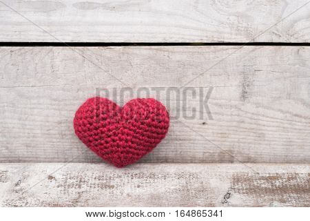 Crocheted heart on a grunge wooden background.