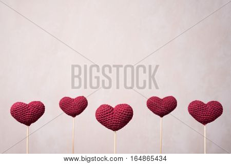 Five crocheted hearts on wooden sticks in a row.