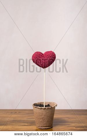 Crocheted heart in a peat glass on a wooden table.