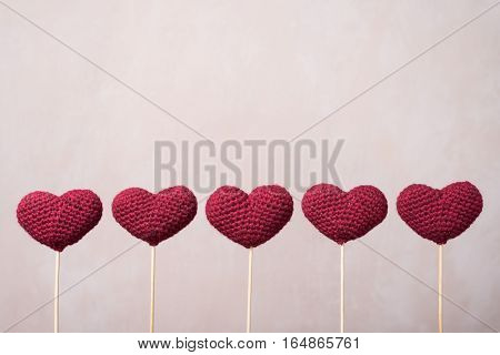 Five crocheted hearts on wooden sticks in a row