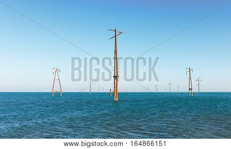 Old abandoned power transmission towers in the sea water