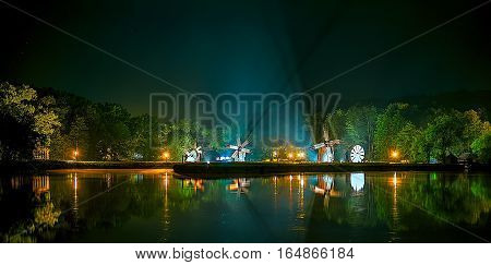 Lake night scene with windmills and reflections on water
