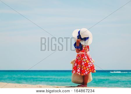 cute little girl with big bag and hat at sea beach