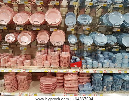 CHIANG RAI THAILAND - NOVEMBER 29 : various brand of pink and blue plastic dishes in packaging for sale on supermarket stand or shelf on November 29 2016 in Chiang rai Thailand.