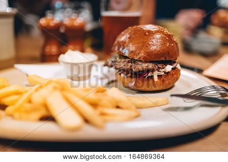 Tasty Grilled Beef Burger With Lettuce And Mayonnaise Served On White Plate With French Fries. Moder