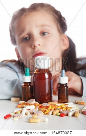Little sick girl does not want to take medication isolated on white