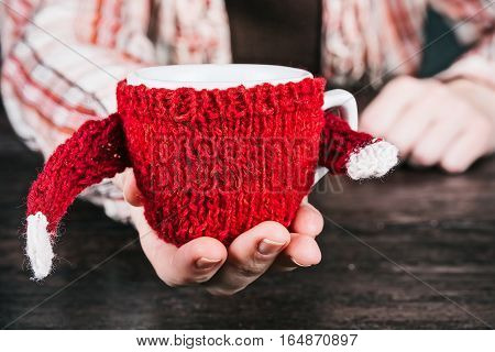 Human hand holding cup outstretching its sweater hand over the table for handshake