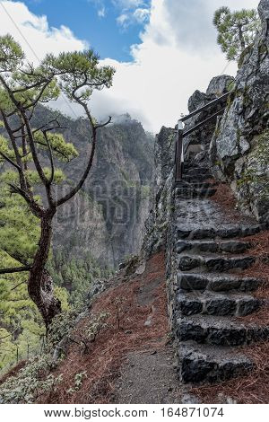 "Cumbrecita mountains in the ""Caldera de taburiente"" national park with its characteristic landscape. Photo shows the rocky stairs of a trail with cumbrecita mountains in the background"