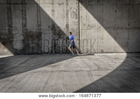 Side view of male runner with blue shirt and smart watch who runs under concrete arcades.