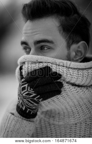 Young man portrait in cold winter weather. He is cold and he wrapped himself in sweater put on gloves. Black and white image.