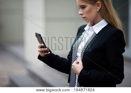 Girl calling on the phone. She holds phone and dials number.