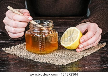 Human hands holding honey dipper and half of lemon. Front closeup view