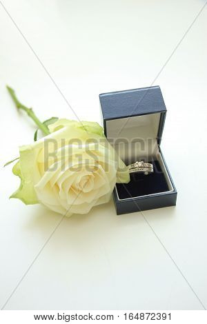 Engagement rings in box and white rose