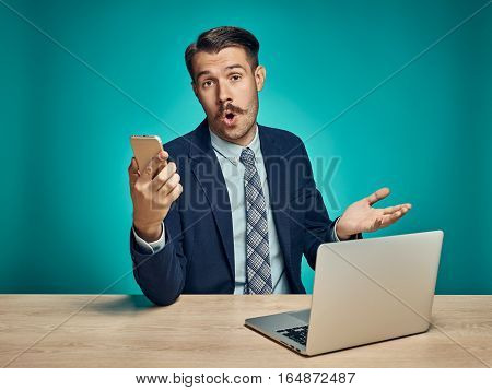The surprised young man in a business suit working on laptop at desk on blue studio background