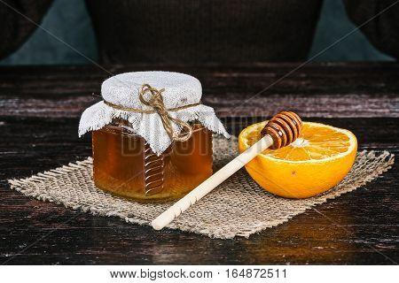 Honey jar and half of orange.  Front closeup view