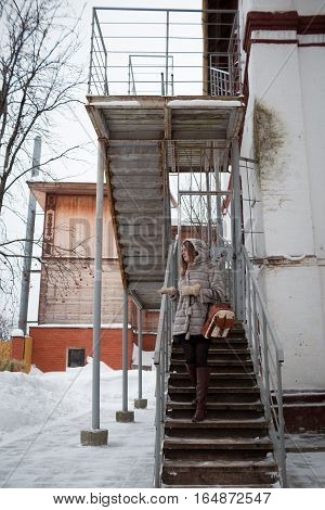 walk around the city: the girl in a gray short fur coat costs on a ladder and looks in a distance