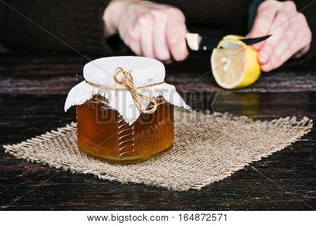 Honey jar on the sackcloth. Human hands slicing lemon on the background. Front closeup view