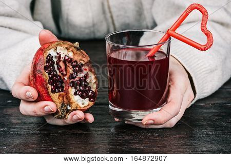 Glass of pomegranate juice with heart-shaped straw and half of pomegranate fruit in human hands. Concept of Valentine's treat