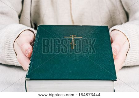 Closed holy bible with orthodox cross in human hands. Closeup front view