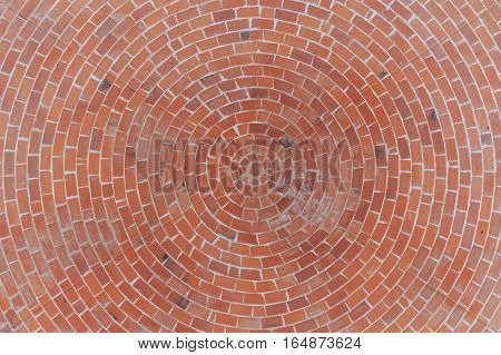 Round stone pavement pattern. Top view of red bricks circular pavement texture