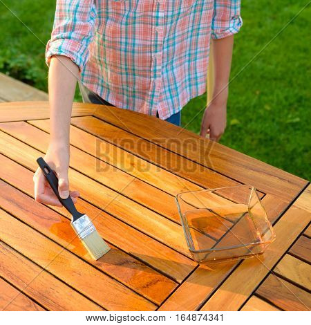 hand holding a brush applying varnish paint on a wooden garden table - painting and wood maintenance oil-wax poster