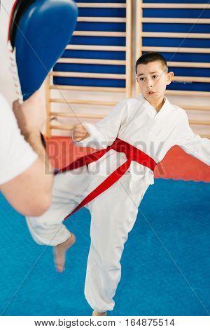 Boy on Tae kwon do training with trainer, toned image