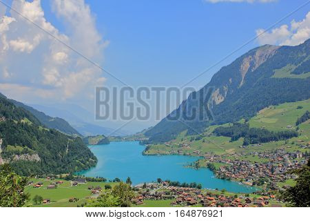 The picture was taken in the Swiss Alps. The picture shows one of the picturesque villages located on the shores of the azure lake.