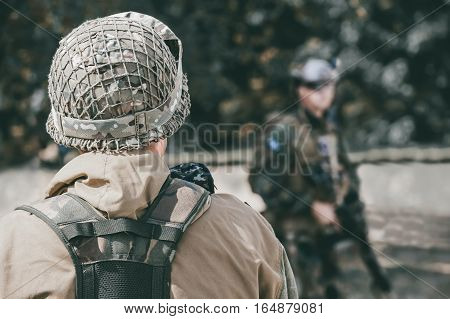 The Soldier In The Performance Of Tasks In Camouflage, Helmet And Holding A Machine Gun,in The Backg