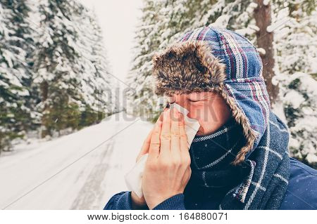 Ill man with paper tissue in winter nature - healthcare and medicine concept