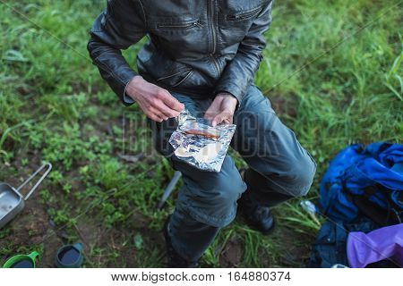 Male Hand Grabbing Bacon From Tinfoil During Hiking Trip. Top View.