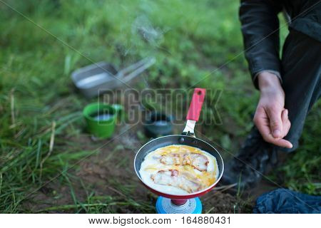 Frying Egg With Bacon On Camp Gas. Close-up Of Male Hand With Pan.