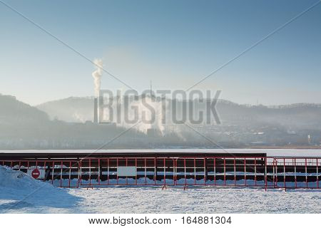 Bank of frozen lake and big steamshop's pipe on background. Smoke is rising up.