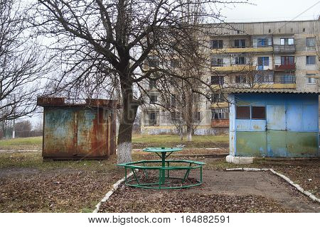 Yard of forsaken house in a ghost town with rusty kiosks round table and abandoned apartment house at background