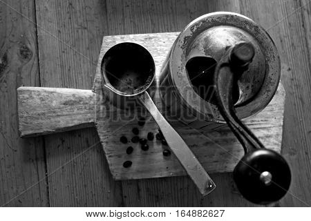 Vintage top view of coffee, pepper or sugar grinder or mill with a mechanical rustic handle, coffee beans and metal turka  on wooden board in black and white style