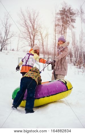 Group of happy chherful people having fun on snow hill. Two women and kid sliding on snow tubes. Winter vacation concept.