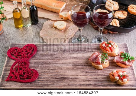 Romantic Dinner. Love. Bruschetta Set For Wine With Tomatoes, Prosciutto, Herbs And Oil On Wooden Bo
