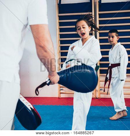 Tae kwon do training with kids, toned image, indoor scene