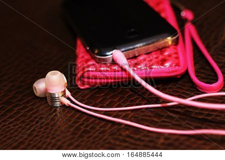 Smartphone and pink headphones sound and song