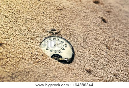 Sands of time. Antique pocket watch with cracked glass, partially buried in sand.